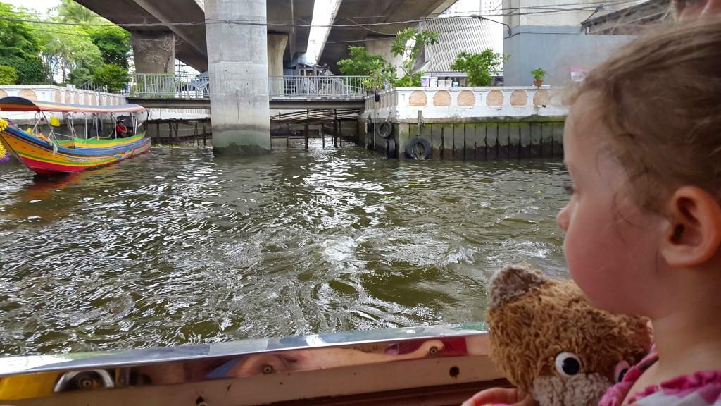 Z večjimi čolni (na sliki levo) zapljujete tudi po kanalih reke, kjer vidite še več lokalnega dogajanja (Bangkok, Tajska)