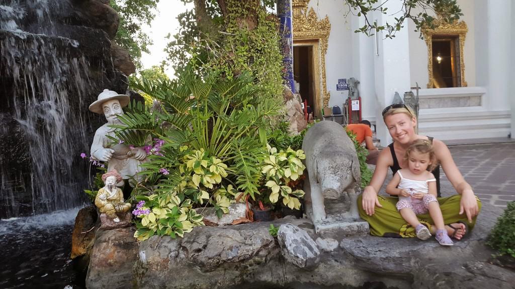 V malem ribniku pred templjem ležečega Bude smo nahranili ogromne ribe. Tempelj  v ozadju (Bangkok, Tajska)