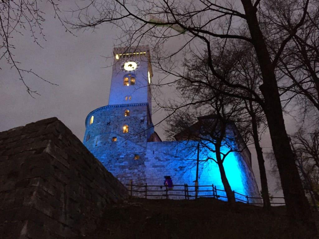 Pogled na pravljično osvetljen grad iz vznožja.