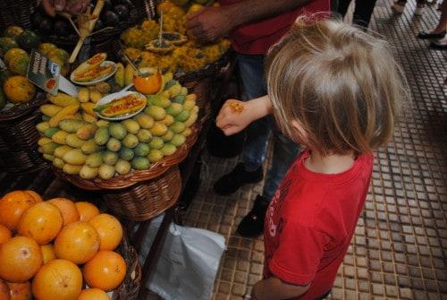 Mulc okuša različne pasijonke na tržnici v Funchalu, Madeira