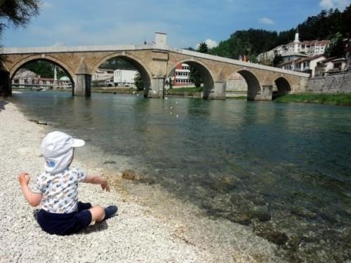 Metanje kamenčkov v vodo pod mostom, v Konjiču, družinski roadtrip po Bosni